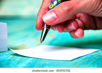 Close up of woman's hand writing on paper