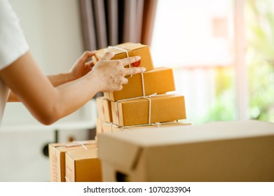 close up of a woman's hands arranging a box of goods to be delivered to customers.