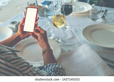 Close up of woman's hands holding cell telephone with blank copy space screen for your advertising text message or promotional content, girl watching on mobile phone during dinner.