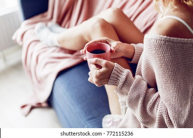 Close up of woman's hands holding a cup of tea . Warm cozy home  mood. Pink knitted sweater. Soft colors.
