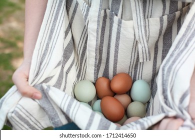 Close up of a woman's hands, holding organic colorful eggs in her apron. Selective focus with extreme shallow depth of field and blurred background.