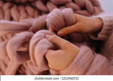 Close up of woman's hands knit. Girl knitting with pink wool big merino warm blanket. Rosy tender natural yarn. Cold winter