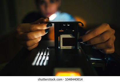 Close up of woman's hands setup slide projector in the dark room