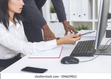 Close up of woman's hands showing a line of report at computer screen to her colleague. Concept of cooperation