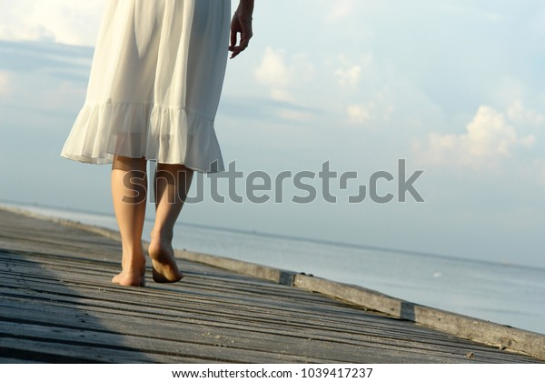 close up of a woman's leg walking on a wooden walkway next to a sea