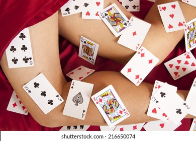A close up of a woman's legs with playing cards all over her legs.