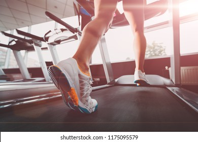 close up womans legs running at the treadmill in the gym against the sunrise. lady wearing white orange blue sneakers. Cardio exercise. concept of healthy lifestyle