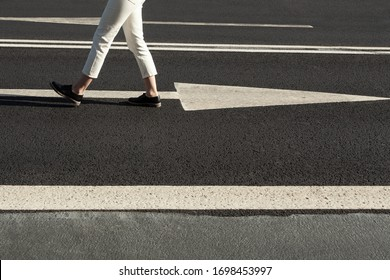 Close up of a womans legs walking in opposite direction from a road sign