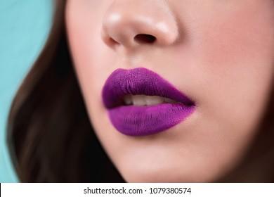 Close up of the woman's open lips. Purple lipstick, lip gloss, cosmetics. Horizontal
