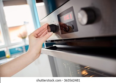 Close up of women hand setting cooking mode or temperature on oven
