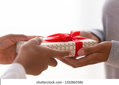 Close up women hands hold gift box loving mom or sister giving present to daughter o friend express love and attention. Happy mother day celebration congratulation, family holidays life events concept