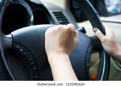 Close up of a women is hands holding a car's steering wheel and honking the horn.