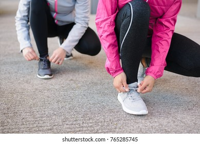 Close up of women lacing sport shoes and getting ready for urban running. Fitness workout and healthy lifestyle concept.