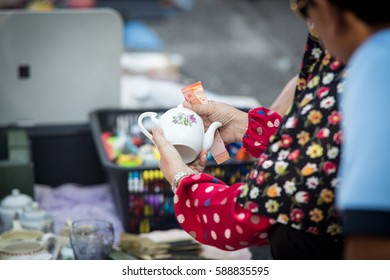 close up of women looking at antique teapot at flea market