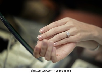 close up of women's finger wearing a diamond ring