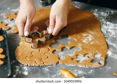 Close up women's hands cooking festive Christmas gingerbread cookies in the home kitchen