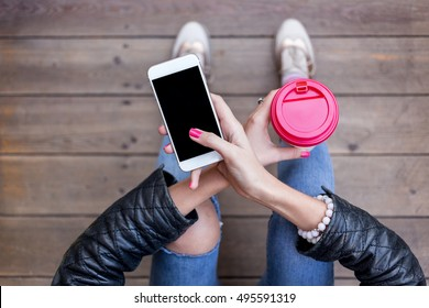 Close up of women's hands holding cell telephone with blank copy space screen for your advertising text message or promotional content. Young hipster girl sitting on Wooden floor and using smart phone