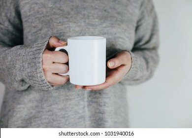 Close up of women's hands holding white mug with blank copy space scree for your advertising text message or promotional content, sweet coffee or tea.