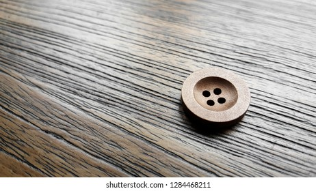Close up wood button on wood background.