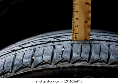 Close up wood ruler measure the tread of black tire