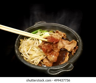 close up wood shopstick keep grill pork with sauce ,slide egg, bean and vegetable in hot pan asian food style in black background