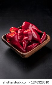 A close up of a wooden bowl full of bright red chili peppers.