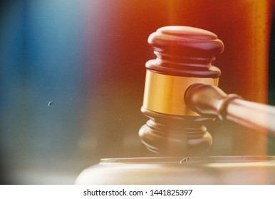 Close up of a wooden brass bound gavel for a judge or auctioneer standing upright on its base against a dark background with copyspace