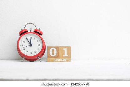 Close up of wooden calendar date 01 January with red alarm clock on white grunge wood table with copy sapce. New Year's Eve 1 January date end of year start the New Year new era.