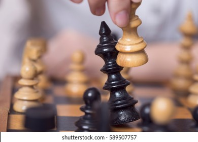 Close up of a wooden chess board and pieces, white queen taking a black king. Selective focus