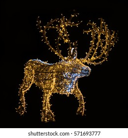 close up of a wooden Christmas reindeer decorated with blue and yellow led lights in the night dark background