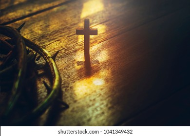 close up of wooden cross and crown of thorns of Jesus against window light on wooden background with copy space, can be used for Christian concept , Easter concept