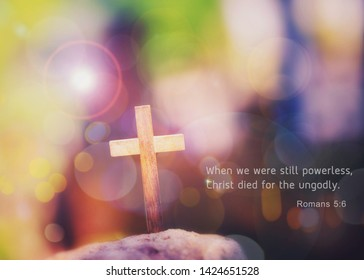 Close up of wooden cross on the rock over blurred colorful  Bokeh  light with word from bible verses, John 3:16 , Christian background with copy space.