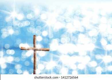 close up wooden cross over sunny bokeh light background