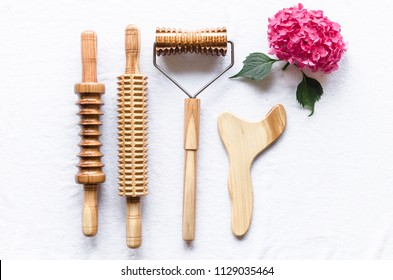 Close up of wooden equipment for anti-cellulite massage on white towel with pink flower bouquet.