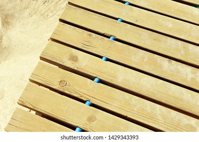 Close up of a wooden footbridge on the beach sand