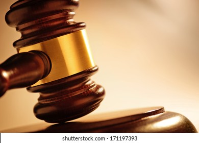 Close up of a wooden judge or auctioneers gavel with a brass band on a wooden base for delivering judgement - Shutterstock ID 171197393