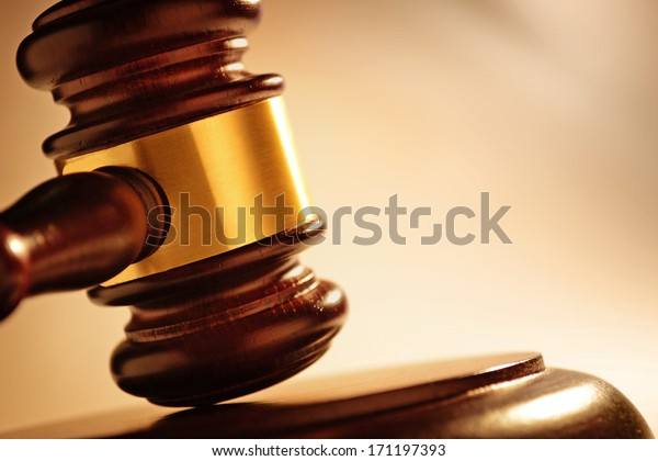 Close up of a wooden judge or auctioneers gavel with a brass band on a wooden base for delivering judgement