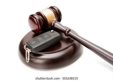 Close up of wooden judge gavel and car keys over soundboard on white background