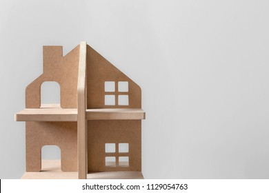 Close up of wooden minature house on bright background with place for text. Symbol of estate, property, investment and development.