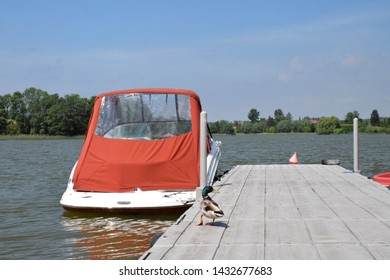 Close up of a wooden pier, marina or jetty with a colorful duck walking on it and a parked white boat with a red cover floating next to it with some dense forest or moor in the distance on a sunny day