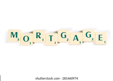 Close up Wooden Scrabble Letter Tiles Forming Mortgage Word Isolated on White Background.