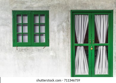 Close wooden shutters on cement background.Green door and window on a concrete wall,Lime Green Window.Green wooden door and shutters close.