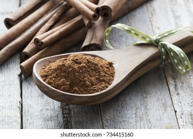 Close up of wooden spoon filled with ground cinnamon in front of  cinnamon sticks.