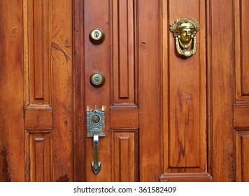 A close up of a wooden stained door showing some deadbolts and decorative knocker and door handle.