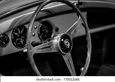 A close up of a wooden steering wheel in a vintage Porsche sports car.