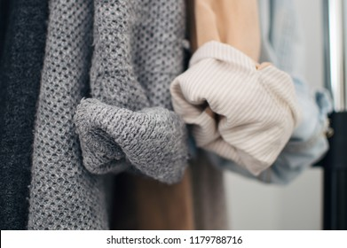 Close up of woolen cardigan, linen and denim jackets rolled up sleeves. Minimal lifestyle, capsule wardrobe. Selective focus, horizontal
