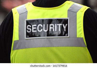 Close up of the word security written on the back of a security guard's yellow vest