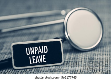 Close up of wording UNPAID LEAVE with stethoscope on wooden table. Medical and health care concept