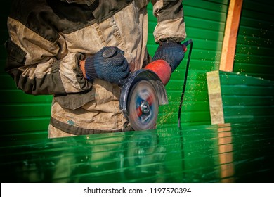 Close up worker cutting metal with angle grinder. Close up of a young  man welder in brown uniform,  welders leathers, grinder metal an angle grinder  at the construction site