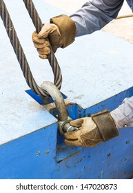 Close up worker fitting bolt anchor shackle with wire rope sling on crane counter weight